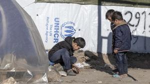 Kolme poikaa leikkii marmorikuulilla Morian pakolaisleirillä.