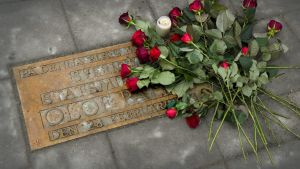 Blommor vid en minnesplakett över Olof Palme