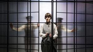 En skådespelare i vitt står mellan två glasväggar som skjuts på plats av suddiga gestalter bakom väggarna.