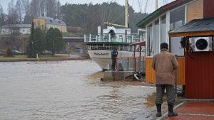 Två män står och fiskar i regnet vid Borgå å.