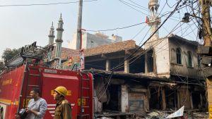 Nedbrända hus i New Delhi 26.2.2020. I bakgrunden en demolerad moské.