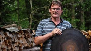 Den tyske korttidsarbetaren Hans Pfister har reparerat sin såg och håller upp ett vässt cirkelblad