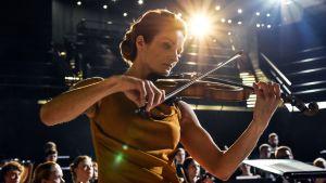 Matleena Kuusniemen hahmo soittaa viulua konsertissa. Taustalla orkesterin jäseniä.