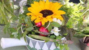Ett blomsterarrangemang med sparris och rädisor i porslinsskål.