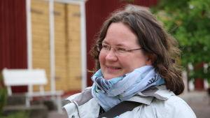 En kvinna med brunt hår och glasögon. Runt halsen har hon en scarf.