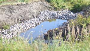 En  konstgjord damm byggd längs ett dike mitt på en åker.