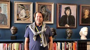 En man står vid en vägg prydd med tavlor och en bokhylla.