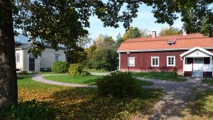 Ett gult och ett rött trähus på en gård.