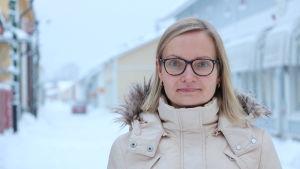 En kvinna med axellångt blont hår och glasögon står på en vinterklädd gata.