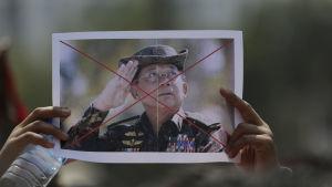 Två händer håller upp ett fotografi av den myanmariska kuppmakaren general Min Aung Hlaing. Bilden är överkryssad med rött.