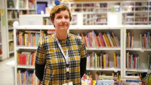En kvinna står framför bokhyllor fyllda med böcker. Det är ett bibliotek.