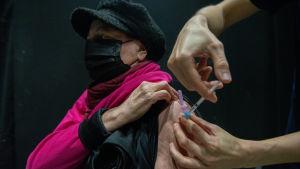 En kvinna får Astra Zenecas coronavaccin.