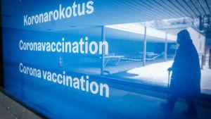 Skylt där det står Coronavaccination. I reflektionen av skylten syns en person som promenerar.