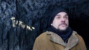 Sol strimmar in i grotta. Jan Jämsén med pälsrock, ser uppåt, uttryckslöst.