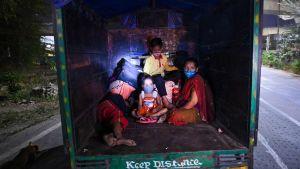 En familj i en lastbil som försöker ta sig hem från New Delhi