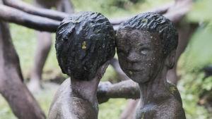 Betonista valetut patsaat: Kaksi lasta tanssii