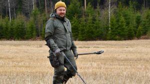 Heikki Räisänen går på en åker med en metalldetektor och letar efter metallföremål