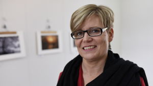 Tina Nylund ler mot kameran med foton i bakgrunden.