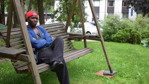 Pauli Sitoi sitter i en trädgårdsgunga