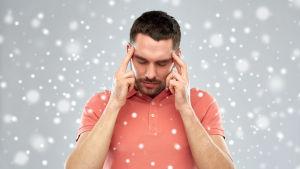 En man som håller sig för huvudet med bägge händer.