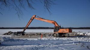 Grävmaskin som gräver på en sandstrand på vintern när det är snö.