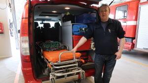 Peter Fihlman står vid utryckningsfordonets baklucka som är utrustad med en bår
