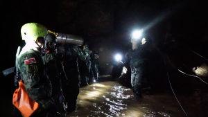 Thailändska militärer bär in förnödenheter i grottan.