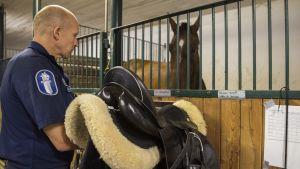 Ratsupoliisi Timo Kossila asettaa satulaa telineeseen Luigi-hevosen karsinan seinää vasten ja hevosen ja Kossilan katseet kohtaavat.
