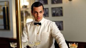 Karaktären Angelo i baren med vit rock och svart fluga.