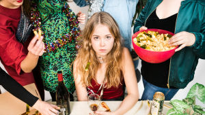 Flicka sitter vid ett bord omgedd av stående kompisar på en hemmafest.