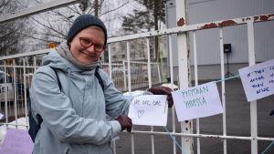 Juudit Hurtig håller upp en lapp vid ett staket. På lappen står det we are one.