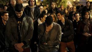 Människor gråter då Notre-Dame i Paris brinner.