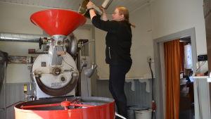 Kvinna häller kaffebönor i en maskin