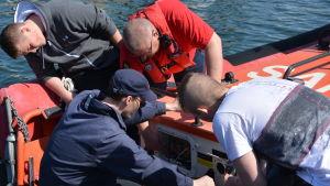 Sjöräddare i Kasnäs granskar sjöräddningsbåtens kopplingar och kablar i motorutrymmet.