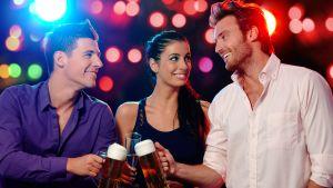 Två snygga män och en snygg kvinna skålar med ölstop på en fest.