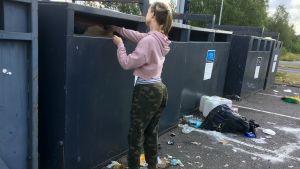 En kvinna sätter in avfall i en behållare vid en sorteringsstation.