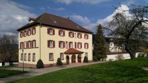 Stauffenberg schloss i Tyskland, ett stort vitt stenhus med röda fönsterkarmar.