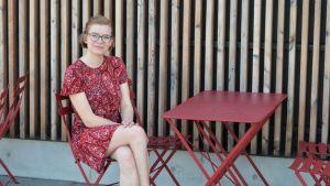 Sofia Wahlroos sitter på en röd bänk.