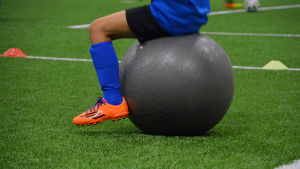 Ett barn sitter på en stor grå gummiboll. Endast benen och fötterna av barnet syns.