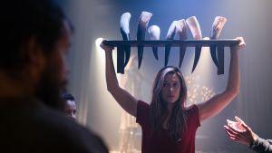 Alfhildr (Krista Kosonen) håller upp en bänk med kohorn fyllda med mjöd.