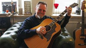 Neumann med en akustisk Gibson gitarr i sitt vardagsrum
