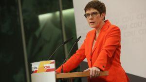 CDU-ledaren står vid ett poedium.