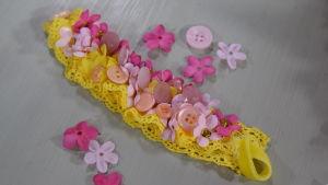 Ett armband av gul spets med rosa detaljer som små tygblommor, udda knappar och pärlor.