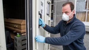 En arbetare vid kyrkogården i Uccle öppnar dörren till en nedkyld container med kistor.