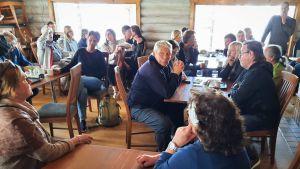 Människor samlade kring bord i en stockstuga.