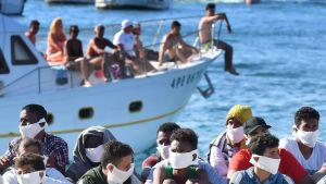 Nyligen anlända migranter satt uppradade på kajen i Lampedusa på onsdagen, medan en turisbåt med italienska turister passerade.