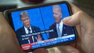 Donald Trump och Joe Biden på en telefonskärm