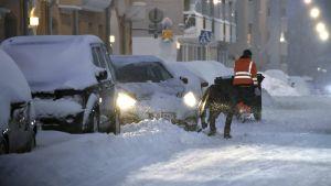 Två personer i orange västar röjer snö på en gata. En bil försöker starta. Alla bilar är täckta av snö och det snöar på bilden. Det är kväll och mörkt.