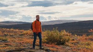 Man i jeans och orange tröja vandrar i fjällandskap som lyser i höstfärger.