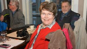 Soile Gustafsson i klädd röd tröja sitter vid ett bord.